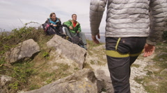 4K Group of friends on a hike sit down to rest on cliff top with coastline view  Stock Footage