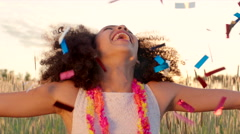 Young girl enjoying confetti rain in the wheat field during sunset - stock footage
