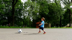 Tracking camera of a little boy with ball in hands running in playground Stock Footage