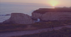 Aerial of couple walking along ocean cliffs at sunset at Shark Fin Cove, Santa Stock Footage