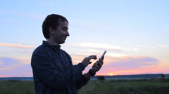 Young man holding a cellphone at sunset. He write sms Stock Footage