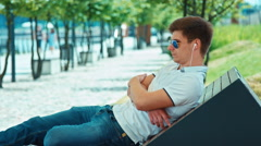 Beautiful student male in sunglasses with headphones sitting on outdoor bench Stock Footage