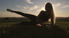 Sports sexy blonde girl model does exercises abdominal workout outdoors in park - stock footage