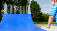 Little boy playing on a skating ramp in a playground Stock Footage