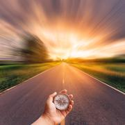 Hand man holding compass on blurred road with sky sunset. - stock photo