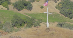 aerial of Wooden cross with american flag waving from it on top of a hill - stock footage