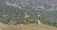 Aerial of Wooden cross with american flag waving from it on top of a hill Stock Footage