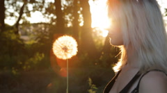 Beautiful Girl blowing dandelion on the meadow at sunset Stock Footage