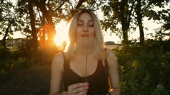 Beautiful Girl blowing dandelion on the meadow at sunset - stock footage