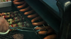 Turing hot dogs on top shelf of grill Stock Footage
