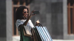 Woman with a shopping bags making a video call via smartphone Stock Footage