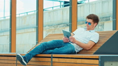Beautiful student male using tablet pc in sunglasses sitting on outdoor bench Stock Footage