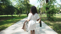 Woman with shopping bags walking in a city park after day shopping Stock Footage