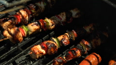 Turning kabobs with tongs on grill Stock Footage