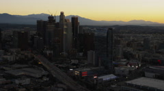 Aerial sunrise view of city buildings with distant mountains Los Angeles Stock Footage