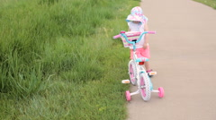 Toddler learning how to ride her first bike. Stock Footage
