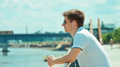 Close up portrait beautiful student male in sunglasses using headphones Stock Footage