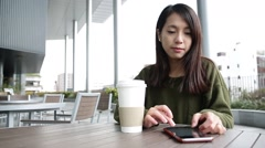 Woman use of mobile phone at outdoor cafe - stock footage