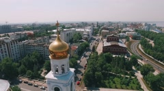 Camera is flying along dome of bell tower, flying over buildings and roads Stock Footage