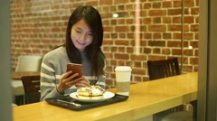 Woman enjoy her cake and use of cellphone inside coffee shop at night Stock Footage