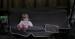 Little Girl is Sitting on the Swing at a Backyard Stock Footage