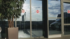 The guy and the girl are going out of the door of the airport. Stock Footage