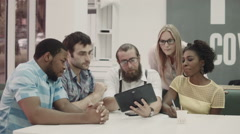 Group of international co-workers using tablet at table Stock Footage