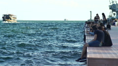 Youths standing on sea quay with ships at sea in slow motion Stock Footage