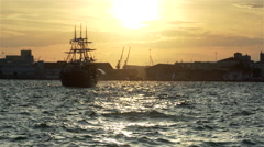 Wooden ship sailing in the bay at sunset in slow motion Stock Footage