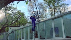 Worker guy in uniform washing glass house with high pressure Stock Footage