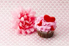 A pink flower beside a pink cupcake with hearts in it Stock Photos