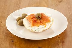 A plate of slice bagel with salmon and olives Stock Photos