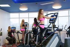 Image of workout in gym. Cute girl poses at camera - stock photo
