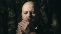 Pensive bald man alone in the forest smokes a cigarette Stock Footage