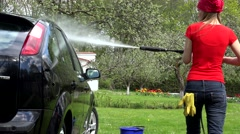 gardener woman washing her car with strong water jet in open air - stock footage