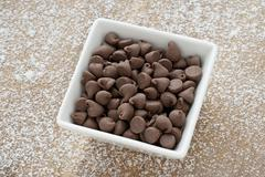 Chocolate morsels on white bowl Stock Photos
