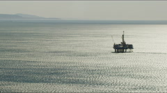 Aerial view at sunrise offshore oil rig California USA Stock Footage