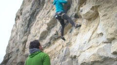 4K Female rock climber beginning a climb on rocky cliff face Stock Footage
