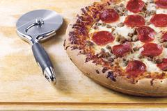 Close up shot of pizza with cutter Stock Photos