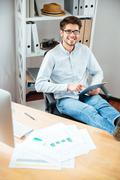 Cheerful young man in glasses using tablet in office - stock photo