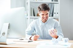 Mad annoyed businessman working and crumpling paper in office - stock photo