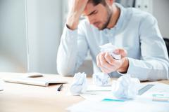 Tired desperate young businessman working and crumpling paper Stock Photos