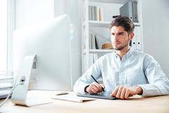 Concentrated young man designer working with computer and graphic tablet - stock photo