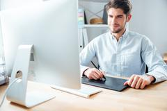 Man designer working using computer and graphic tablet at workplace - stock photo