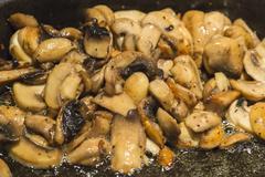 Fried mushroom in frying pan Stock Photos