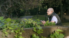Bald man with tablet in ancient city park Stock Footage