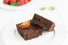 Close up of chocolate brownie cakes topped with strawberries and arranged on  Stock Photos