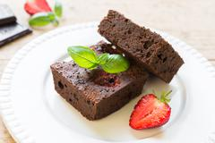 Close up of chocolate brownie cakes topped with strawberries and arranged on  - stock photo