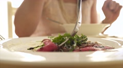 Young woman eating carpaccio in the restaurant. Close-up of food and fork 4K Stock Footage