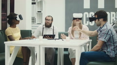 Three people in futuristic virtual reality glasses talking to man with tablet Stock Footage